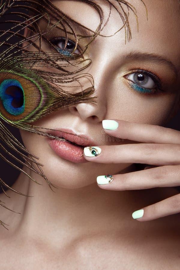 有明亮的构成的美丽的女孩,修指甲设计和孔雀在她的面孔用羽毛装饰 艺术钉子 免版税库存照片