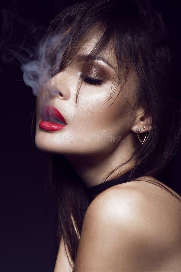 有明亮的构成的美丽的性感的深色的女孩,红色嘴唇,从嘴的烟 秀丽表面 库存照片