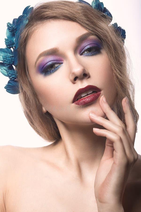有明亮的构成的美丽的白肤金发的女孩和在她的头发的紫色蓝色花 秀丽表面 免版税库存图片