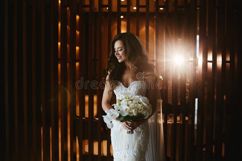 有明亮的构成的美丽,肉欲和性感的深色的式样女孩在有花花束的时兴的白色鞋带礼服在她的 图库摄影