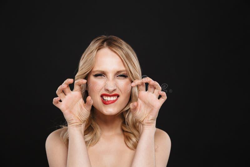 有明亮的构成红色嘴唇摆在的白肤金发的挥动的咆哮的妇女被隔绝在黑墙壁背景 库存图片