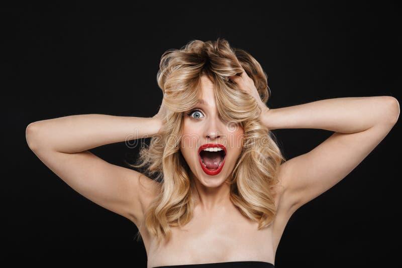 有明亮的构成红色嘴唇摆在的震惊年轻白肤金发的妇女被隔绝在黑墙壁背景 免版税库存图片