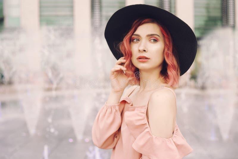 有明亮的桃红色卷发和一个黑海滩帽子的一个女孩在喷泉的背景站立 有美丽的一个女孩轻拍 免版税图库摄影