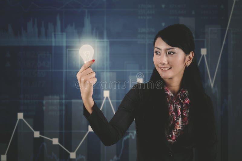 有明亮的电灯泡和成长图表的女实业家 免版税库存照片