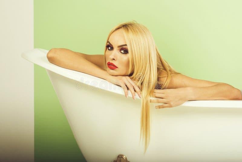 有明亮的红色唇膏的热情的白肤金发的女孩在白色卫生间里 库存照片