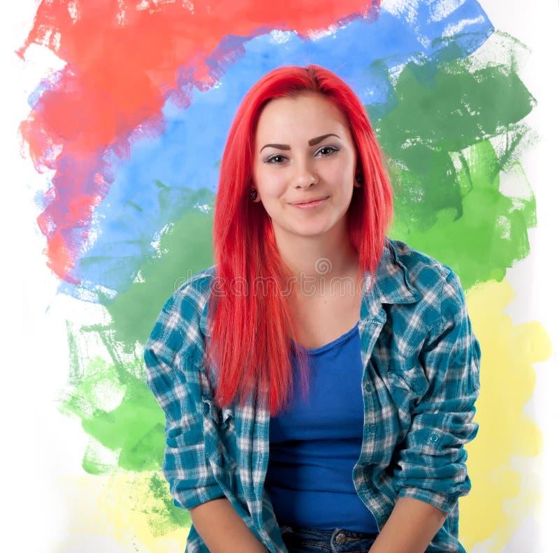 有明亮的红色头发的女孩在五颜六色的背景 免版税库存照片