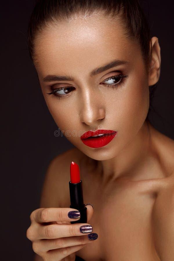 有明亮的红色嘴唇和唇膏的美丽的妇女在手中 免版税库存图片