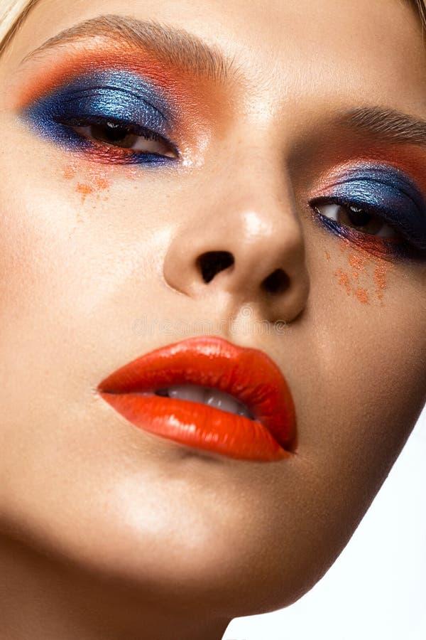 有明亮的色的构成和橙色嘴唇的美丽的女孩 秀丽表面 免版税库存照片