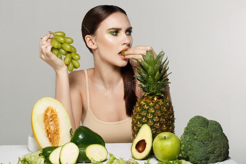 有明亮的艺术构成的健康美丽的深色的女孩吃葡萄的 库存图片