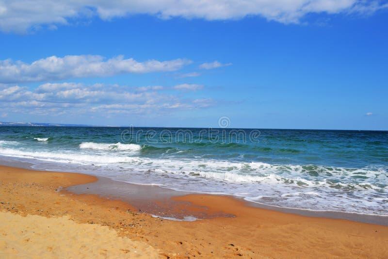 有明亮的蓝天的明亮的青绿色海在一个晴朗的夏天d 库存图片