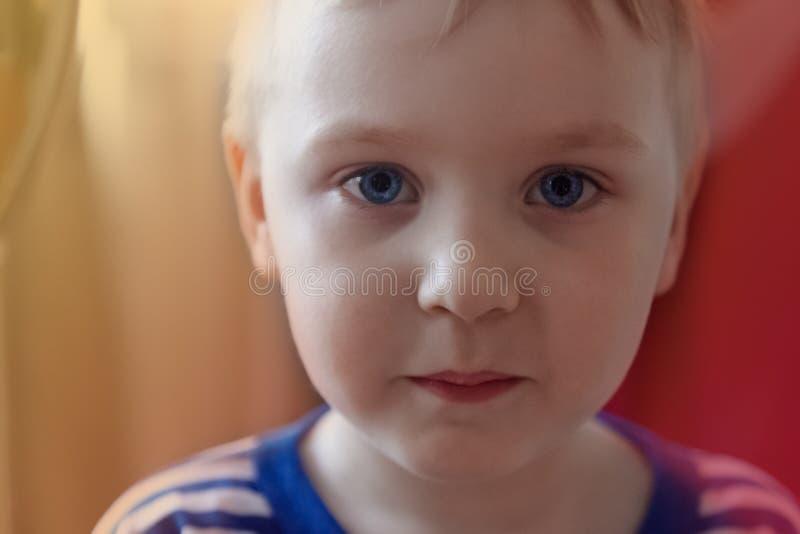 有明亮的蓝眼睛神色的俏丽的逗人喜爱的白种人男婴对照相机 强的情感,严肃的面孔表示 库存照片