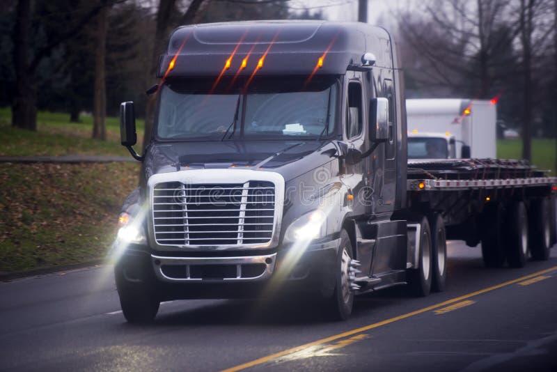 有明亮的车灯和平床的大现代半卡车 库存照片