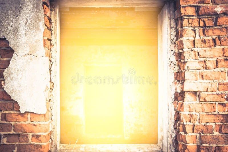 有明亮的黄灯的破裂的砖墙从与光的作用的入口在隧道尽头 图库摄影