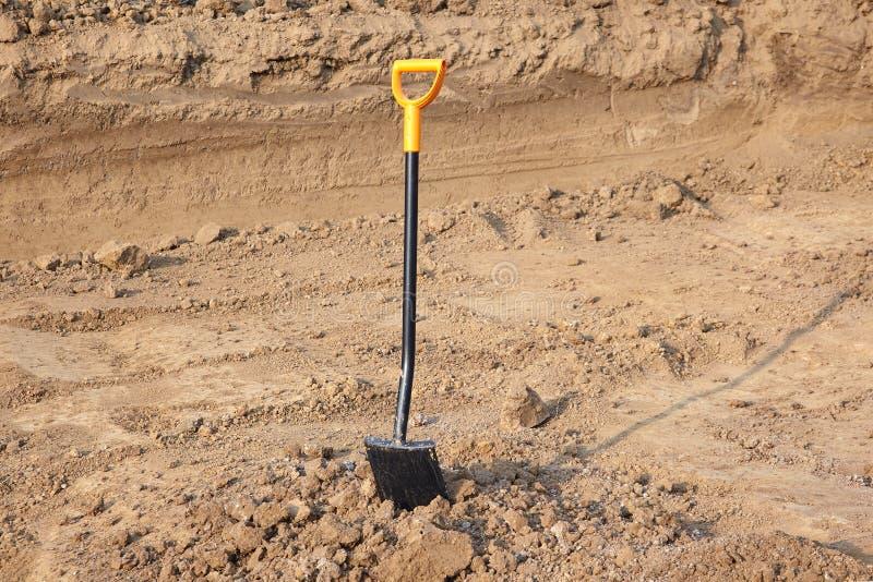 有明亮的黄色把柄的一把铁锹被困住对地面 被研的工作,挖掘 免版税库存图片