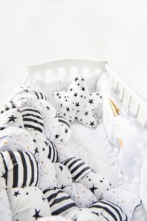 有星状坐垫和补缀品橡皮奶嘴毯子的舒适婴儿床有星和黑条纹的 库存图片