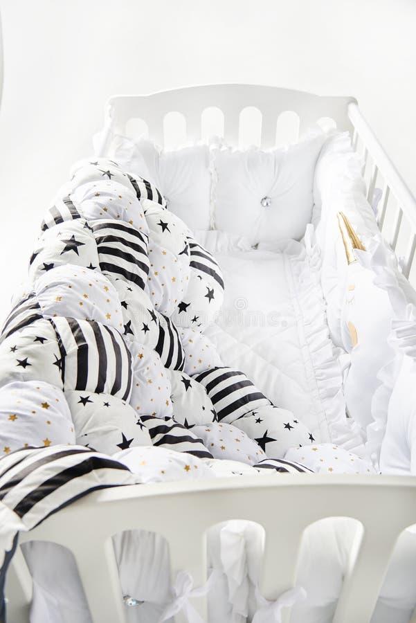 有星状坐垫和补缀品橡皮奶嘴毯子的舒适婴儿床有星和黑条纹的 免版税库存照片