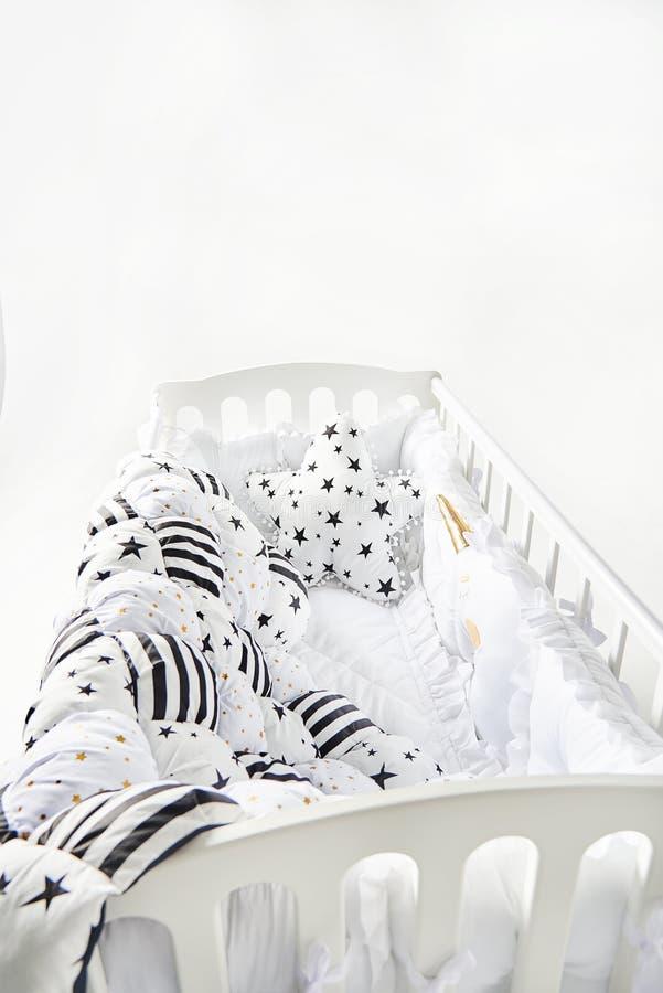 有星状坐垫和补缀品橡皮奶嘴毯子的舒适婴儿床有星和黑条纹的 免版税库存图片
