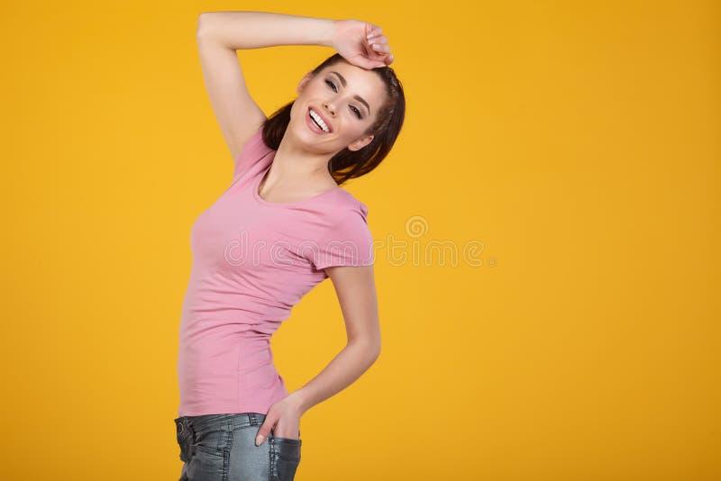 有春天帽子的妇女反对黄色背景 库存图片