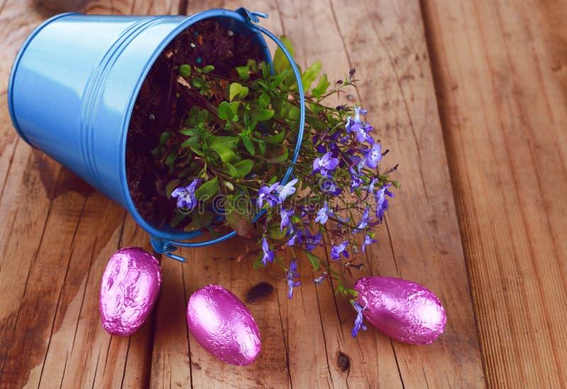 有春天花和复活节彩蛋的蓝色土气桶在木背景 免版税库存图片