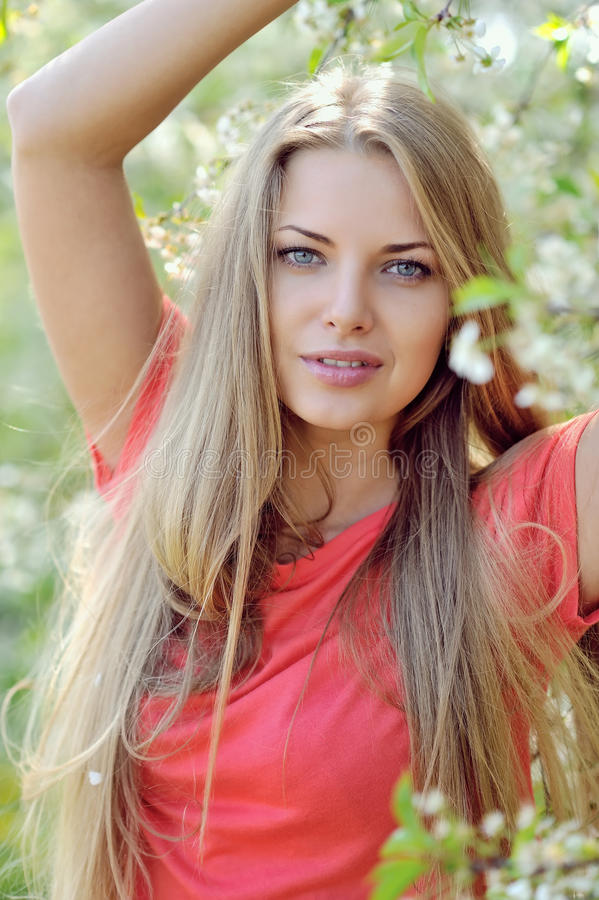 有春天花的美丽的微笑的妇女 免版税库存照片