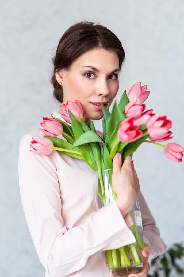 有春天郁金香的美丽的少妇开花花束 微笑举行的愉快的女孩开花,桃红色郁金香 春天画象 免版税库存照片