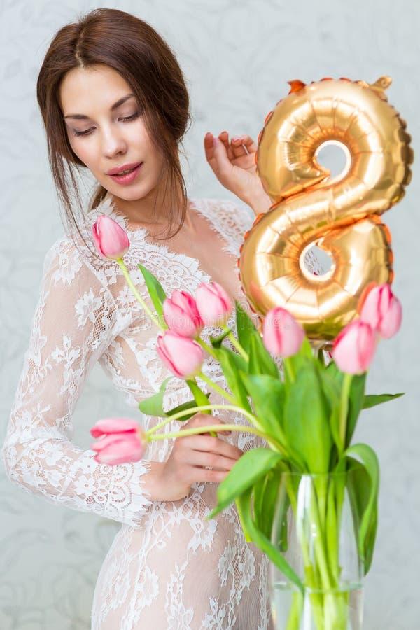 有春天郁金香的美丽的少妇开花花束 微笑举行的愉快的女孩开花,桃红色郁金香 春天画象 库存照片
