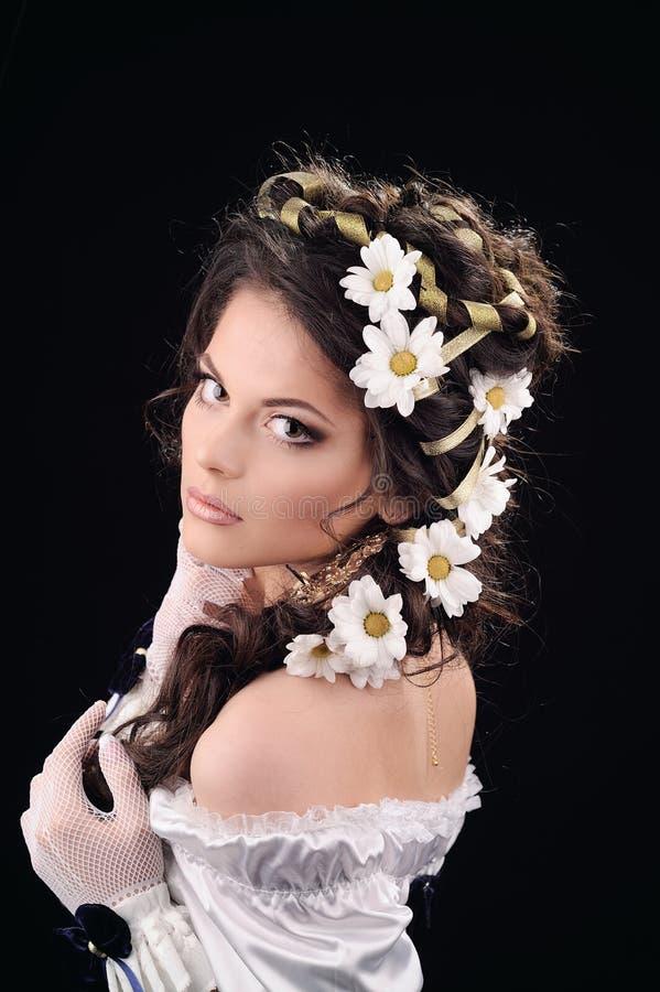有春黄菊的女孩在黑色的头发 库存照片