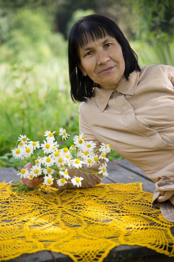 有春黄菊和钩针编织的桌的妇女 库存图片