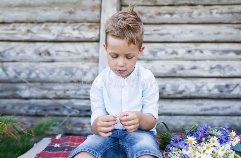 有春黄菊的一个英俊的男孩做一个愿望 免版税图库摄影