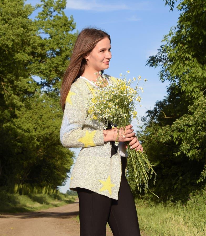 有春黄菊花束的年轻美丽的女孩  大麦领域的一名妇女 库存照片