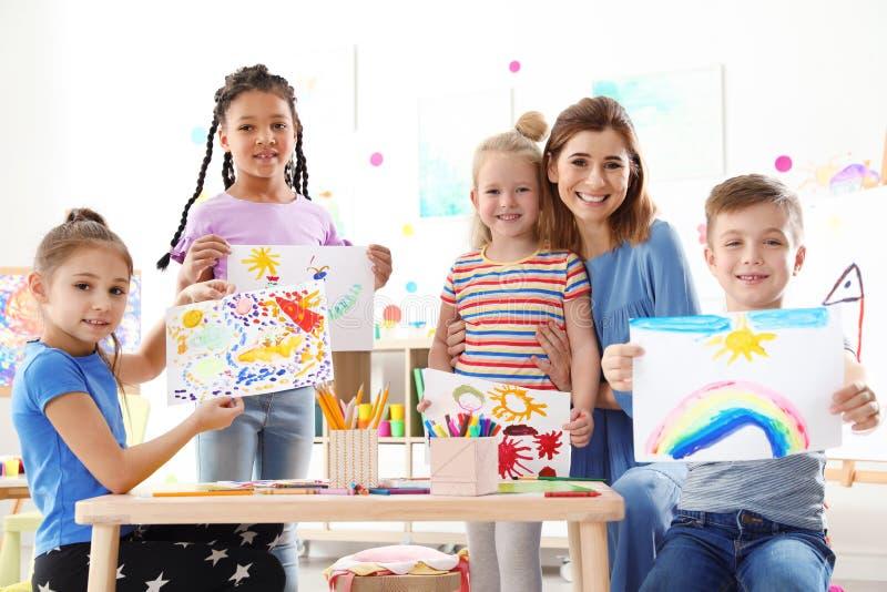 有显示他们的绘画的老师的逗人喜爱的小孩在教训 库存图片