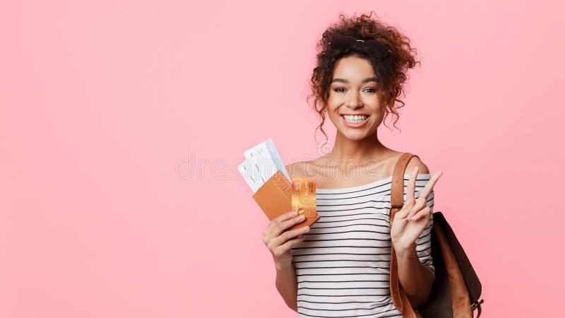 有显示和平姿态的机票的愉快的女孩 免版税库存图片