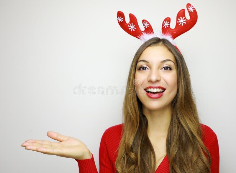 有显示您的产品的驯鹿垫铁的微笑的圣诞节女孩 图库摄影