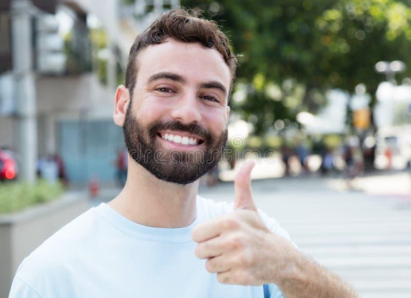 有显示拇指的胡子的白种人人室外在城市 免版税库存照片
