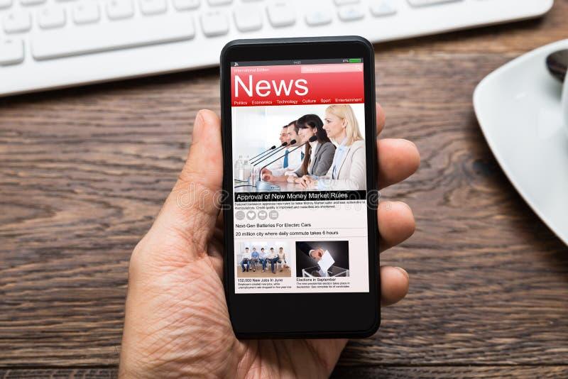 有显示新闻的手机的人手 免版税图库摄影