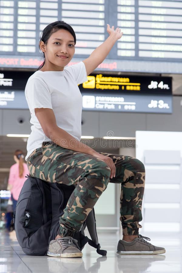 有显示标志的背包的旅行的妇女 免版税库存图片