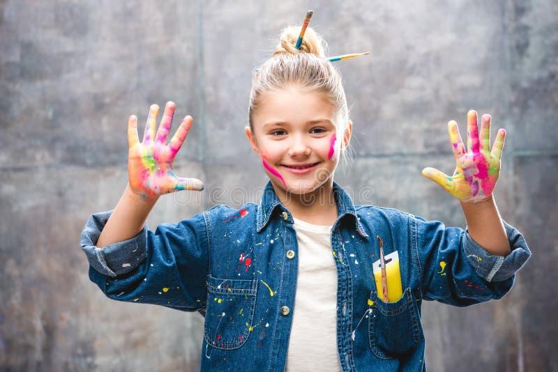 有显示棕榈的被绘的面孔的女小学生艺术家在油漆和微笑 免版税库存图片