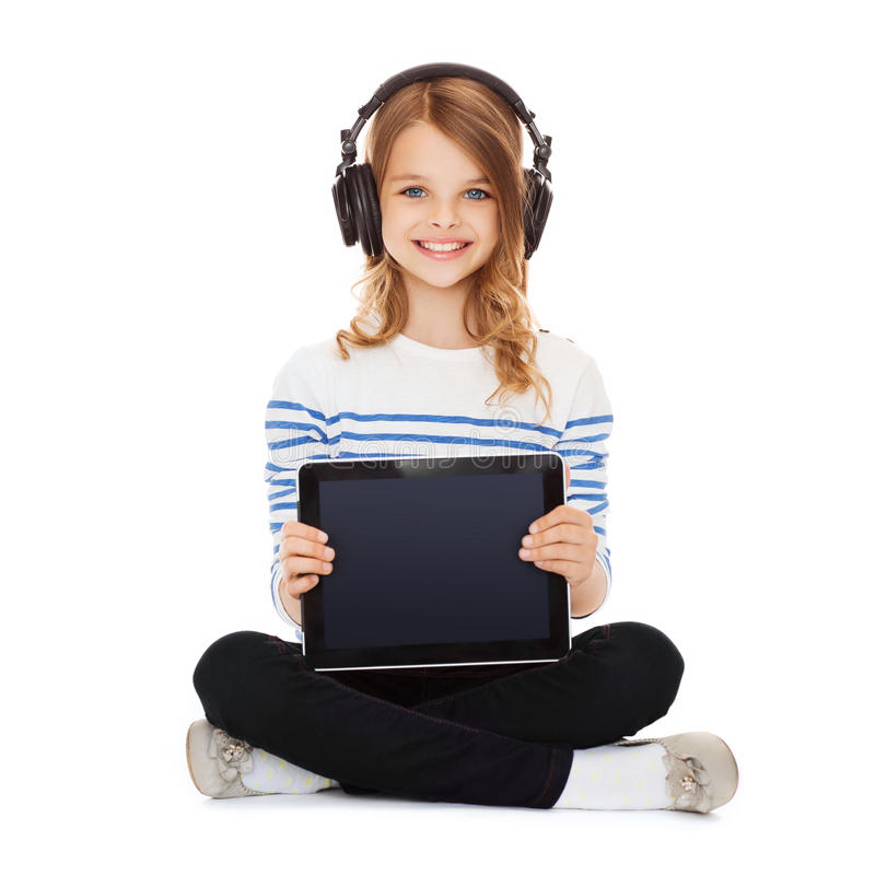 有显示片剂个人计算机的耳机的孩子 免版税库存照片