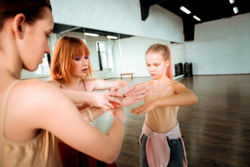 有显示移动的红色头发的美丽的舞蹈老师对她的学生 库存照片