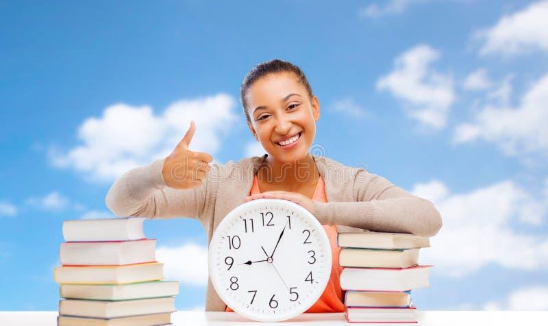 有显示赞许的书和时钟的学生 免版税库存图片