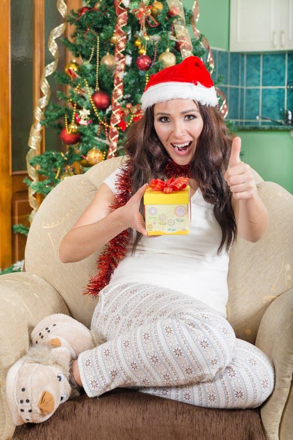 有显示赞许的圣诞节礼物的甜少妇 免版税库存照片