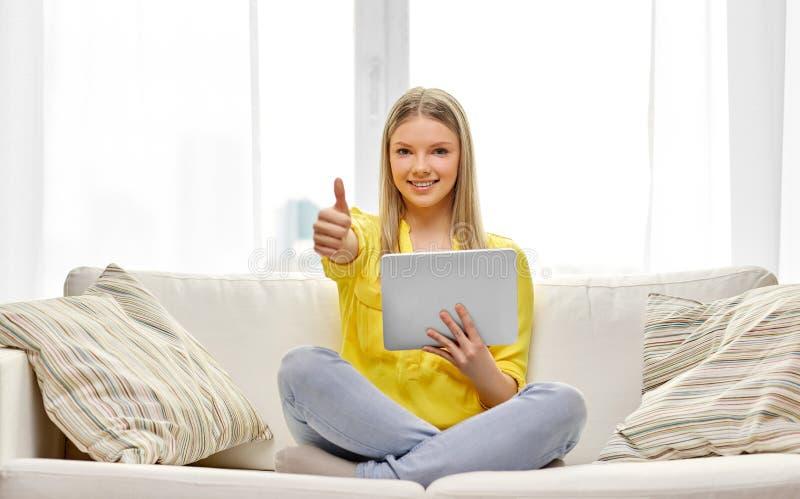 有显示赞许的平板电脑的年轻女人 免版税库存图片