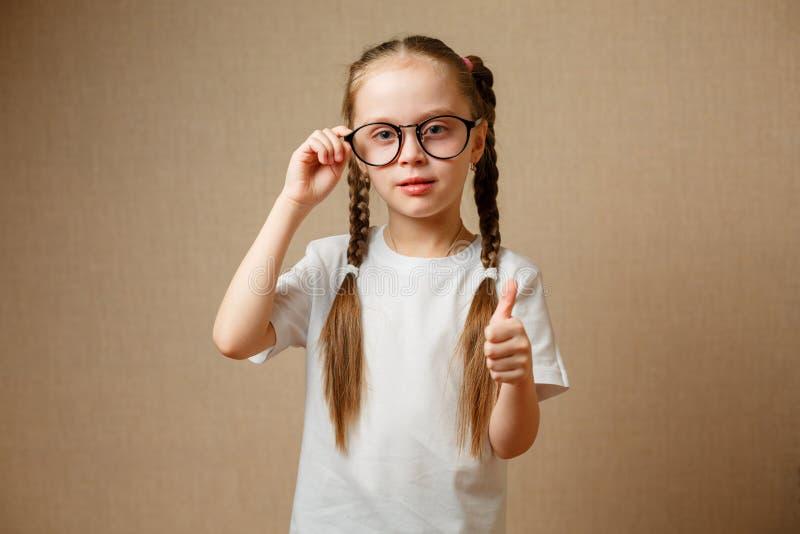 有显示赞许的黑镜片的微笑的逗人喜爱的小女孩 库存照片