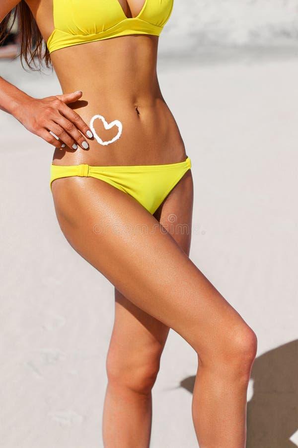 有晒黑化妆水的妇女以心脏的形式在黄色比基尼泳装的 免版税库存照片