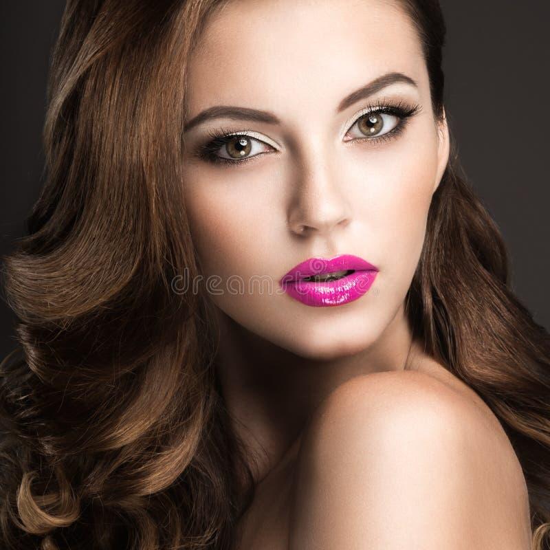 有晚上构成、桃红色嘴唇和卷毛的美丽的妇女 秀丽表面 免版税库存图片