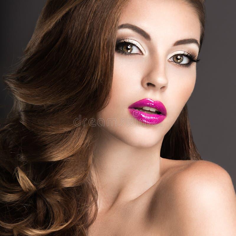 有晚上构成、桃红色嘴唇和卷毛的美丽的妇女 秀丽表面 免版税图库摄影