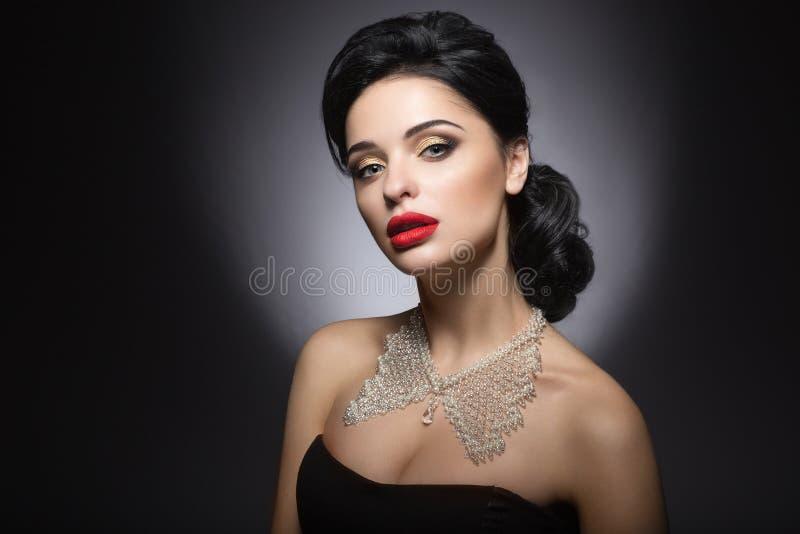 有晚上构成、红色嘴唇和晚上发型的美丽的妇女 秀丽表面 库存照片