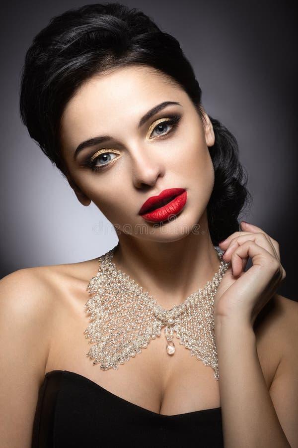有晚上构成、红色嘴唇和晚上发型的美丽的妇女 秀丽表面 库存图片