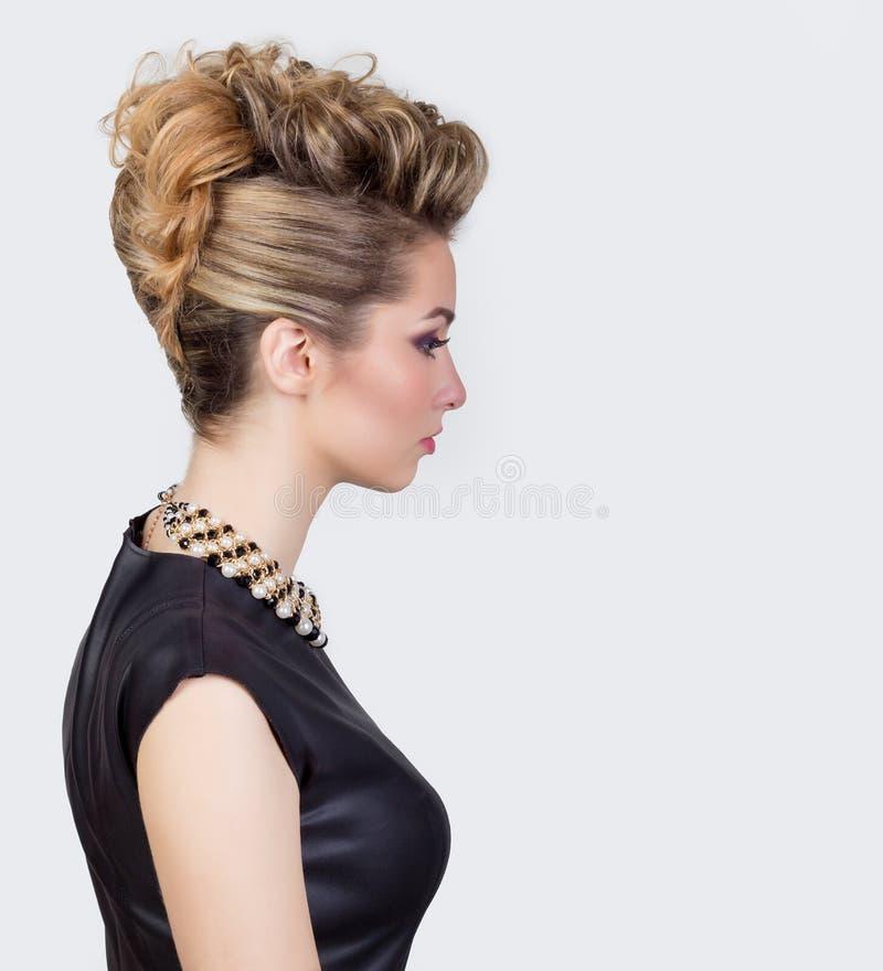 有晚上构成和沙龙发型的美丽的少妇 注视发烟性 党的复杂的发型 库存照片