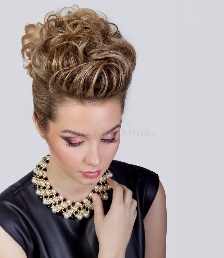 有晚上构成和沙龙发型的美丽的少妇 注视发烟性 党的复杂的发型 库存图片